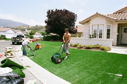sand being putt into synthetic lawn