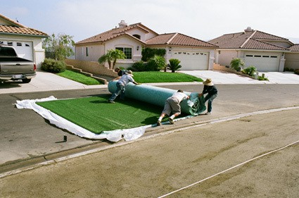 synthetic turf being rolled out on street
