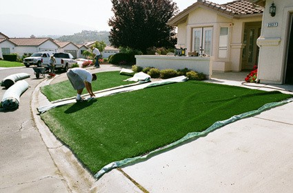 synthetic grass being cut into position on lawn